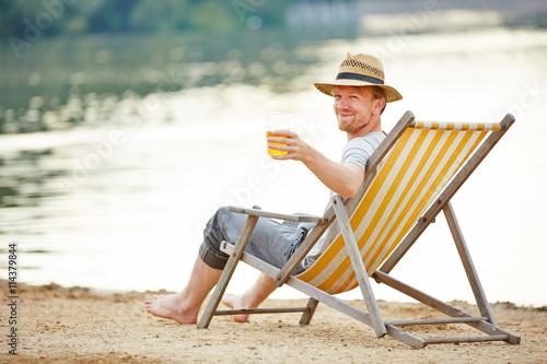 Mann trinkt Bier im Liegestuhl