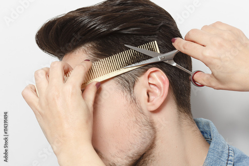 Closeup portrait of handsome young man having haircut in studio Fototapet