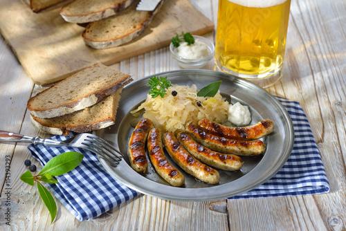 Nürnberger Rostbratwürste mit Kraut und Meerrettich traditionell auf dem Zinnteller mit Brot serviert - Fried Bavarian sausages from Nuremberg with sauerkraut and horseradish served on a pewter plate