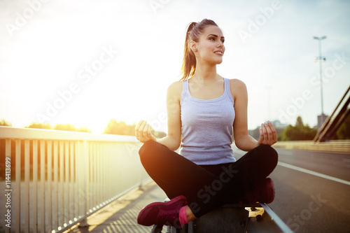 Woman relaxing next to a busy road, challenge concept Wallpaper Mural