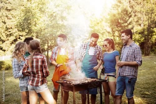 Plakat Młodzi ludzie grillują na zewnątrz