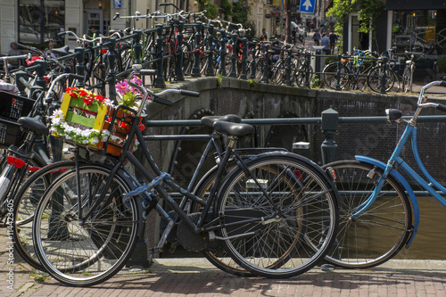 Fotobehang Fiets Bike with flower basket on the street near the canal in Amsterdam in Europe