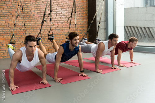 Fototapeta  Fit four men training body in gym