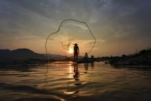 Fisherman Throwing Net In Mekong River During Sunset