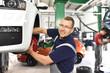 fröhlicher automechaniker repariert Bremsen am Fahrzeug in einer Werkstatt // car mechanic repairs brakes of a car in a garage