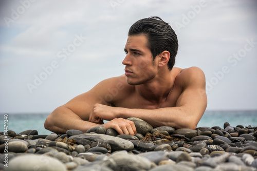 obraz dibond Young shirtless athletic man laying down on pebbles