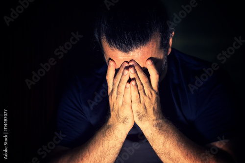 Fotografía  Depressed, sad man covering his face with his hands