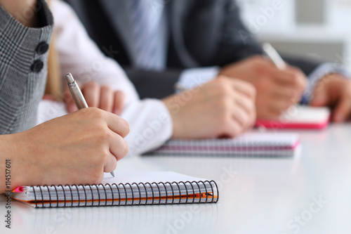 Close up view of students or businesspeople hands writing someth