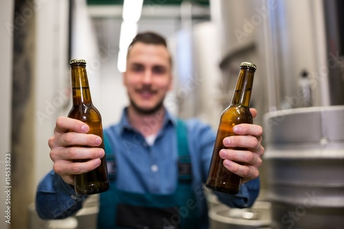 Foto  Brewer holding two beer bottle