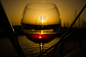 Panel Szklany Wino Sunset over marina with fine glass of wine