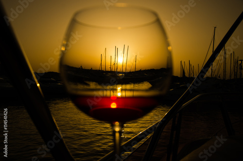 Sunset over marina with fine glass of wine - 114541426