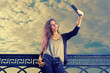 Pretty young female fashion model takes travel selfie at sky with clouds background