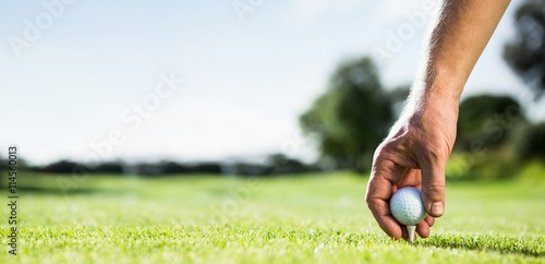 Deurstickers Golf Golfer placing golf ball on tee