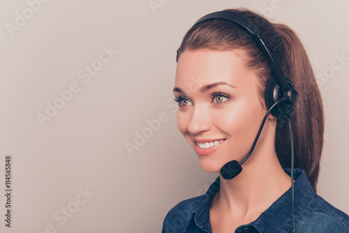 Valokuva  Pretty smiling secretary  in headphones isolated on gray backgro