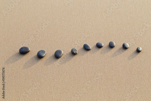 Poster de jardin Zen pierres a sable set of hot stone on white sand calm beach in backbone shape. sel