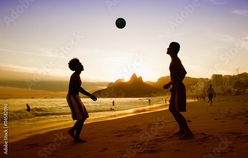 Платно  Two guys loves playing soccer at beach at Rio de Janeiro