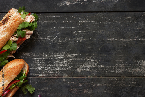Poster Snack Two tuna sandwich on dark wood background