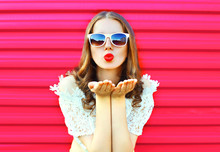 Woman In Sunglasses Sends An Air Kiss Over Colorful Pink Backgro