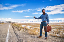 Bearded Hitch Hiker Thumbing For A Ride On An Empty Nevada Road