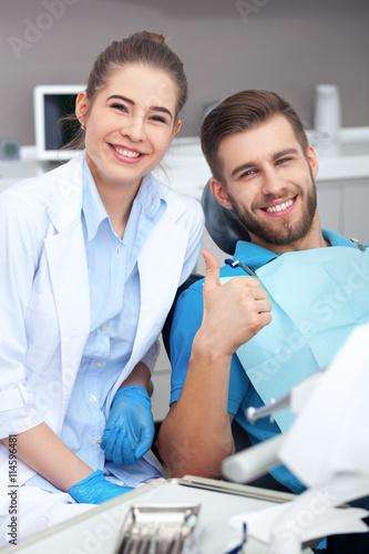 Fototapeta Happy young man in a dentist's chair giving a thumbs up. obraz na płótnie