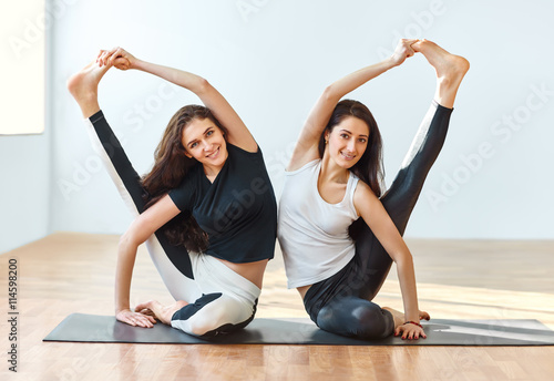 Foto  Two young women doing yoga asana compass pose