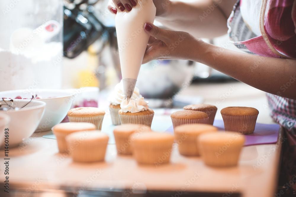 Photo  Woman making creamy top of cupcakes closeup. Selective focus.