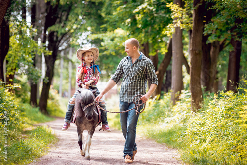 Beautiful little girl on a pony with his father. Wallpaper Mural
