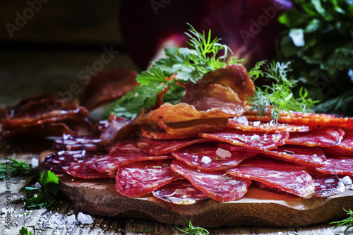 fototapeta na ścianę Sausage platter with herbs and spices on a vintage wooden backgr