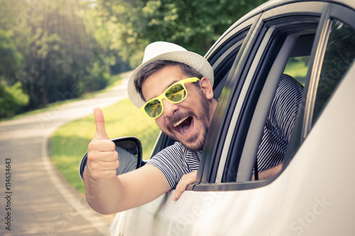 Fotografía  Young man wearing hat and sunglasses showing thumbs up from driver's seat through opened window