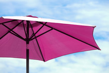 Dark Pink Parasol On Blue Coudy Sky