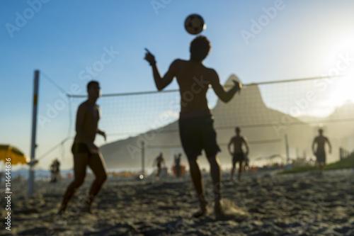 Plakat Nieostre sceny sylwetki Brazylijczyków gry futevolei (footvolley) na tle zachodu słońca z Dois Irmaos Góra dwóch braci na plaży Ipanema, Rio de Janeiro, Brazylia
