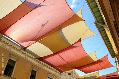 Fotografie, Obraz  Street decorated with colored canvas awnings