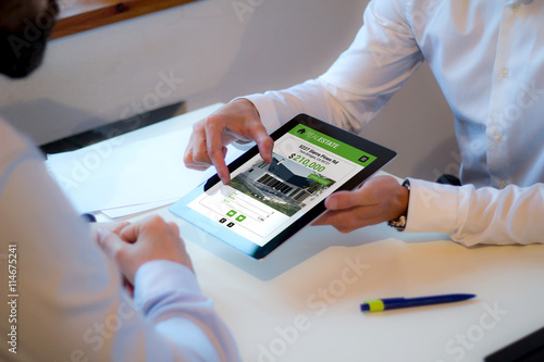 Valokuva  Real estate agent showing man a house in a website