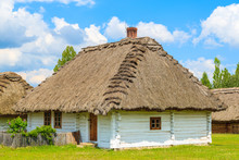 An Old Rustic Cottage House On Green Meadow In Open Air Museum In Tokarnia Village, Poland