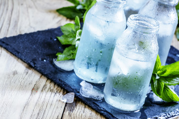 Very cold mineral water with ice in a misted glass bottles, dark