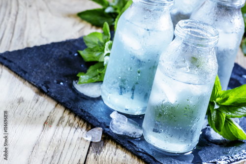 Photo sur Toile Eau Very cold mineral water with ice in a misted glass bottles, dark