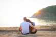 Loving couple sitting on the beach. A loving couple meets sunset on the beach. Love. A family. Relations. Romance. Happiness.