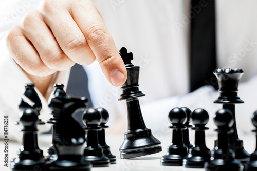 Photo  Hand of businessman playing chess