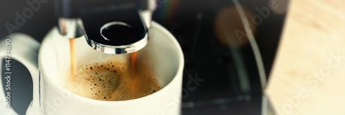 Fotografiet Close up of coffee maker machine pouring brewed hot Espresso