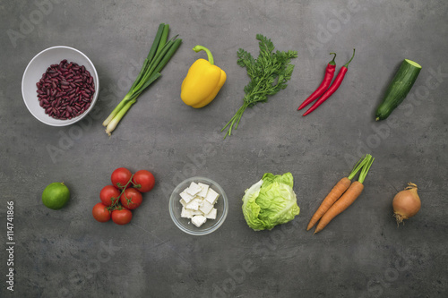 Poster Aromatische Fresh ingredients. Top view on vegetables, red beans and cheese in bowls on grey kitchen table.