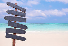Wood Signs On The Beach. Sea And Blue Sky Background