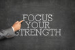 Focus Your Strength text on blackboard with businessman hand pointing