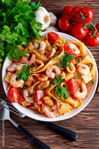 fototapeta na ścianę Tasty Pappardelle pasta with shrimp, Squid, mussel, tomatoes and herbs.