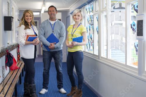 Canvas Print Three Teachers in School Corridor