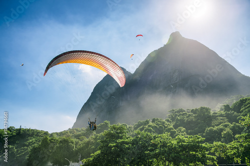 Paraglider passes along the misty greenery of Pedra da Gavea Mountain on its way to land at São Conrado Beach in Rio de Janeiro, Brazil