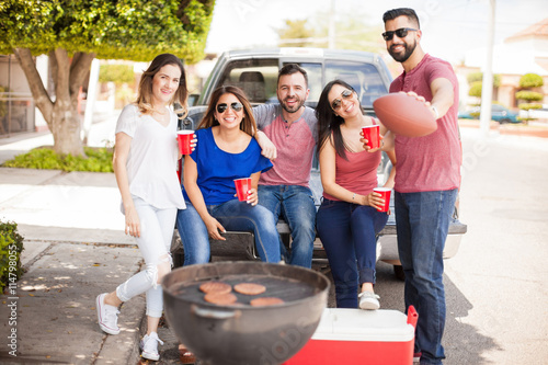 Football fans tailgating at a game and drinking