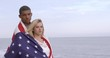Attractive mixed-race young couple looking serious while wrapped in United States flag at a California beach. Medium shot, recorded hand held in slow motion at 60fps