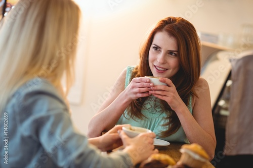 Foto  Happy woman listening to friend at coffee shop