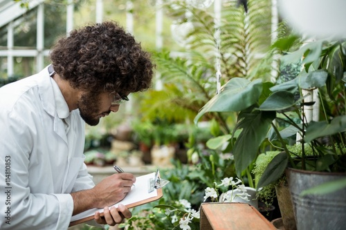 Photo  Male scientist writing in clipboard while examining plants