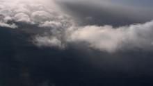 Tilting Flight Through Wispy Clouds At Edge Of Gray Cloud Mass
